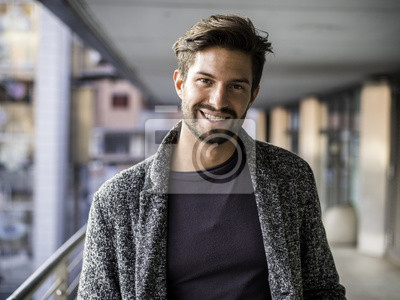 Fototapeta Jeden przystojny młody człowiek w miejskim otoczeniu w europejskim mieście, stojąc i uśmiechając się do kamery szczęśliwy