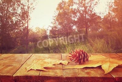 Fototapeta Jesienią tle opadłych liści nad drewnianym stole i lasu backgrond z obiektywem wyrównania i zachodu słońca
