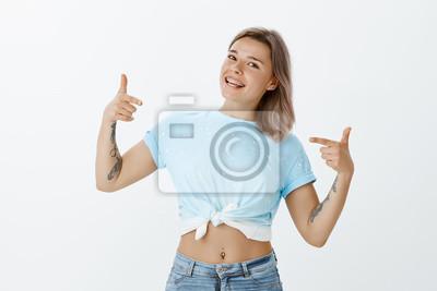 Jestem tym, czego potrzebujesz. Portret pewność beztroski atrakcyjna kobieta w przycięte góry z kolczykiem brzuch, wskazując palcami karabinami na siebie, przechylając głowę i uśmiechając się szeroko,