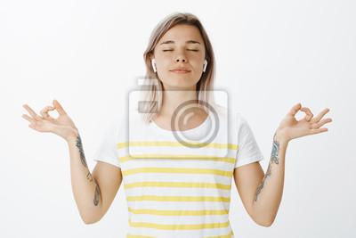 Joga, styl życia i koncepcja młodzieży. Portret zrelaksowany radosny atrakcyjna kobieta w słuchawki bezprzewodowe, stojąc z rozprzestrzeniać się w obie strony ręce w gest zen, uśmiechając się i zamyka