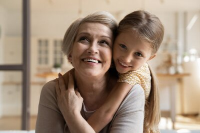 Fototapeta Joyful small 7s kid girl cuddling from back laughing old middle aged grandmother, enjoying tender sweet moment together at home. Happy older retired woman spending weekend with little granddaughter.