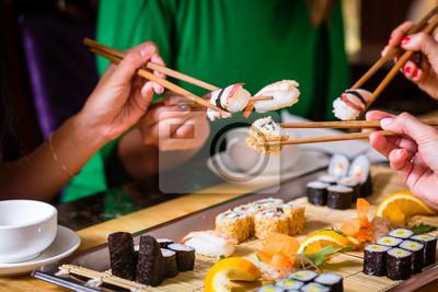 Fototapeta Junge Leute Essen Sushi w Asia Restaurant