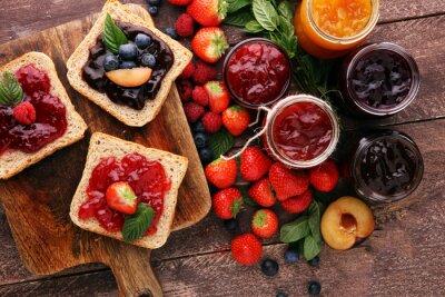 Kanapki z śliwką, truskawkowym dżemem i świeżymi owoc na drewnianym tle ,.