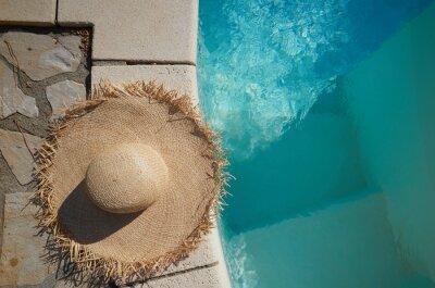 Fototapeta Kapelusz na słońce leży na krawędzi basenu
