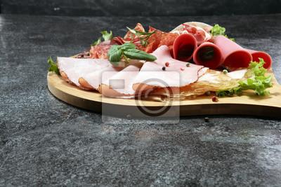 Karmowa taca z pysznym salami, kawałkami pokrojonej szynki, kiełbasy i sałatki. Talerz mięsny z wyborem.