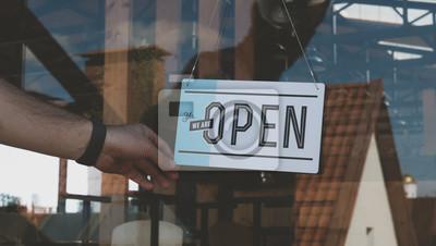 Fototapeta Kaukaski mężczyzna zamienia znak z zamkniętego do otwarcia na drzwiach wejściowych jego małej kawiarni. Koncepcja małych firm