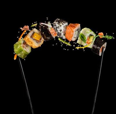 Fototapeta Kawałki sushi umieszczone między pałeczkami na czarnym tle