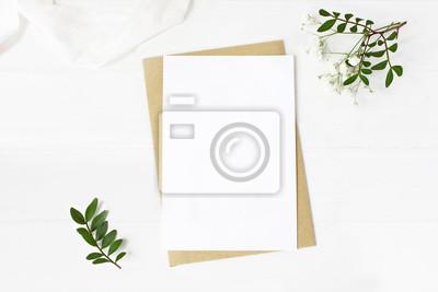 Fototapeta Kobieca papeteria ślubna, scena makiety pulpitu. Puste karty z pozdrowieniami, koperty rzemieślnicze, kwiaty oddech dziecka, jedwabne wstążki i oddziałów lentisk. Stary biały drewniany stołowy tło. Pł