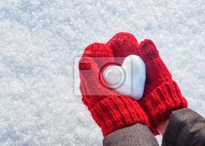 Fototapeta Kobiece ręce w dziane rękawiczki z sercem śniegu w zimowy dzień. Walentynki tło.