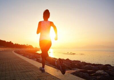 Fototapeta kobieta biegacz sportowiec działa na wschód słońca nad morzem
