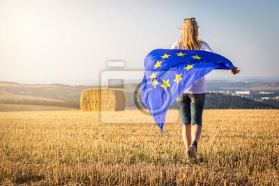 Fototapeta Kobieta działa z macha flagą Unii Europejskiej na wsi