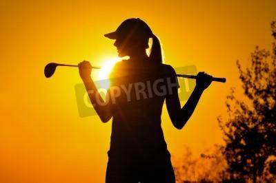 Fototapeta kobieta gracz w golfa tee off podczas zachodu słońca sylwetki