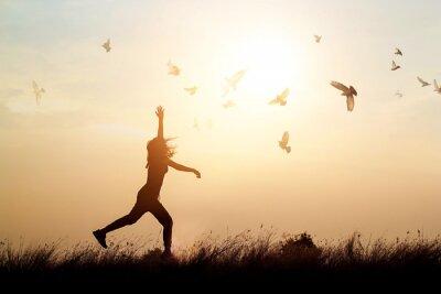 Fototapeta Kobieta i latające ptaki cieszyć się życiem w naturze na tle słońca