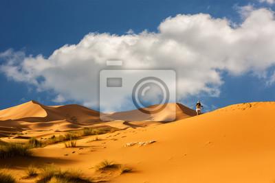 Kobieta idzie przez wydmy Sahary, Maroko