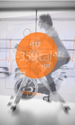 Fototapeta Kobieta jedzie rower treningowy z futurystycznym interfejsem pokazując los