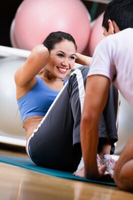 Fototapeta Kobieta robi situps z trenerem w siłowni szkolenia