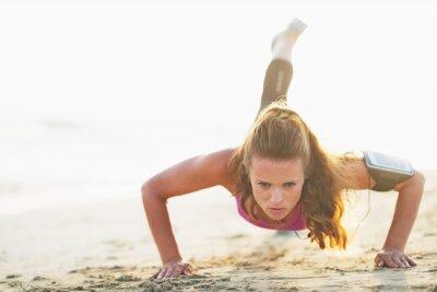 Fototapeta Kobieta sportowiec robi push up na plaży