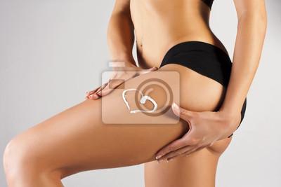 Kobieta stosowania kremu nawilżającego na nogach. Idealna kobieca postać