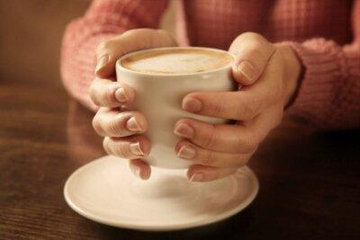 Kobieta trzyma filiżankę kawy, zbliżenie