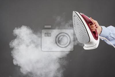 Fototapeta Kobieta trzyma żelazo z kontrparą na szarym tle