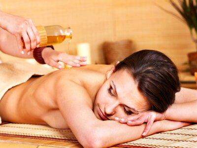 Fototapeta Kobieta uzyskiwanie masażu w bambusa spa.