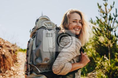 Fototapeta Kobieta z plecakiem wycieczkuje w naturze