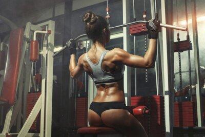 Fototapeta Kobieta zaangażowana w symulatorze w siłowni