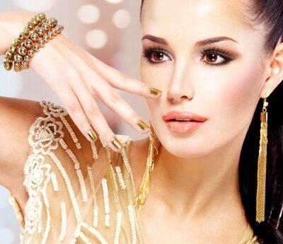 Fototapeta Kobieta ze złotymi paznokciami i piękna biżuteria złota