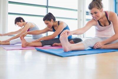 Fototapeta Kobiety rozciągające jogi w klasie