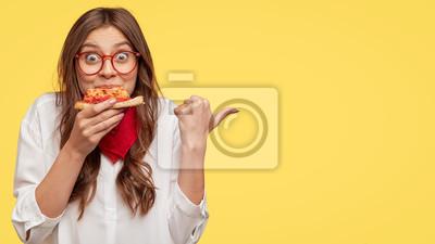 Fototapeta Koncepcja czasu na lunch. Atrakcyjna wesoła kobieta je pyszną włoską pizzę, zaskoczona wspaniałym smakiem, wskazuje kciukiem na bok, pokazuje, gdzie znajduje się pizzeria, proponuje odwiedzić i zjeść