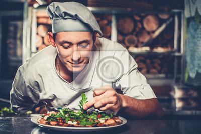 Fototapeta Koncepcja żywności. Przygotowanie tradycyjnej włoskiej pizzy. M? Oda u? Miechni? Ta kucharz w bia? Ym jednolitego i szarym kapeluszu udekorowa? Gotowe naczynie z zielonym zió? Rucola wn? Trza nowoczes
