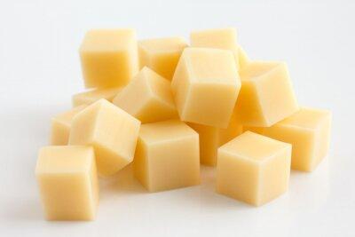 Fototapeta Kostki żółtego sera ułożone losowo na białym tle.