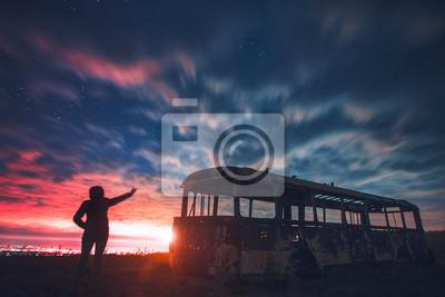 Krajobraz z niebieskim niebem i żółtym światłem. Dziewczyna patrzeje nocy miasto.