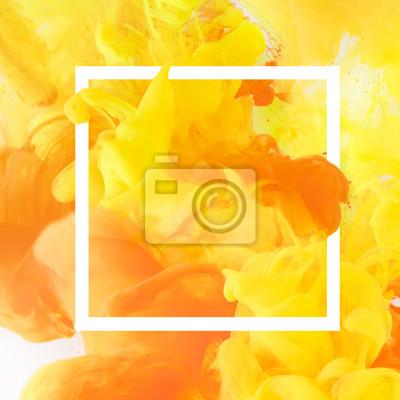 Fototapeta Kreatywny projekt z płynącą żółtą i pomarańczową farbą w białej kwadratowej ramie