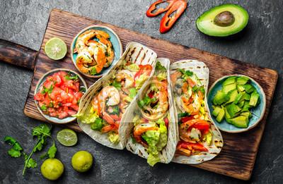 Fototapeta Krewetki tacos z salsą, warzywami i awokado. meksykańskie jedzenie