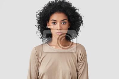 Fototapeta Kryty ujęcie poważnej, ciemnoskórej freelancerki ma fryzurę Afro, przyjemny wygląd, ubrany w beżowy casualowy sweter, działa daleko w domu, cieszy się domową atmosferą. Koncepcja pochodzenia etniczneg