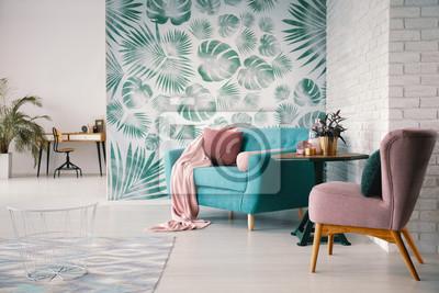 Fototapeta Krzesło i turkusowa sofa w zielonym salonie z liśćmi tapet i stołu. Prawdziwe zdjęcie