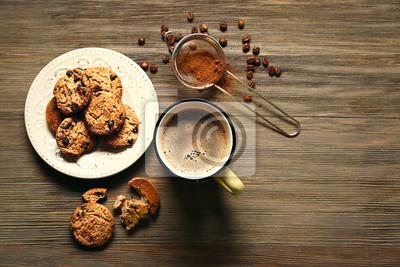 Kubek kawa z ciastkami na drewnianym stole