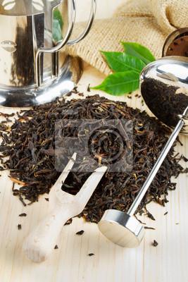 kupie czarna herbata, czajnik, łopatka drewniana na stole