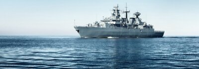 Fototapeta Large grey modern warship sailing in still water. Clear blue sky. Baltic sea, Germany. Global communications, international security theme. Panoramic image