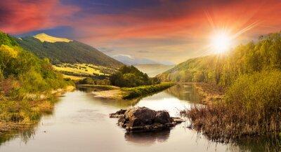 Fototapeta las rzeka z kamieni i trawy na zachodzie słońca
