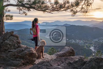 Fototapeta Latynoska wędruje z psem o zachodzie słońca w Górach Skalistych w pobliżu Denver, Kolorado, USA