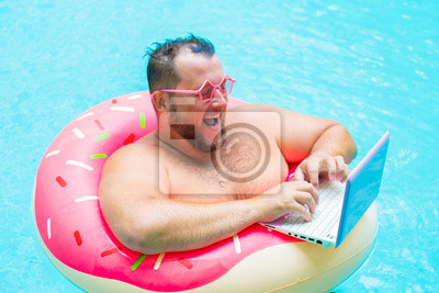 Fototapeta laughing Fat funny man in pink inflatable circle in pink glasses works on a laptop in a swimming pool