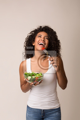 Fototapeta Laughing woman eating healthy salad over light background