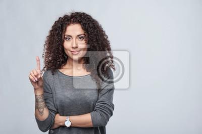 Fototapeta Liczenie ręczne - jeden palec. Kędzierzawa kobieta wskazuje up przy puste miejsce kopii przestrzenią