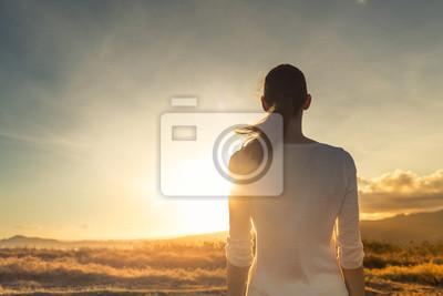 Fototapeta Life is beautiful. Woman standing facing a beautiful golden sunrise.