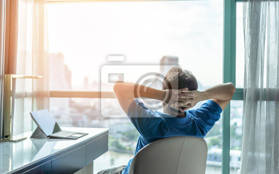 Fototapeta Life-work balance and city living lifestyle concept of business man relaxing, take it easy in office or hotel room resting with thoughtful mind thinking of life quality looking forward to cityscape