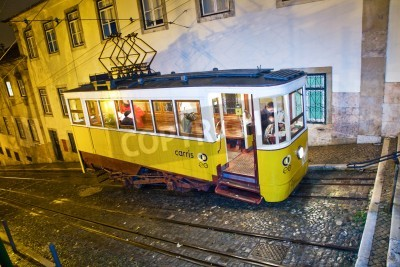 Fototapeta LISBON, PORTUGAL - DECEMBER 29: Traditional yellow tram downtown Lisbon by night on December 29, 2008. Trams are used by everyone and also keep the traditional style of the historic center of Lisbon.