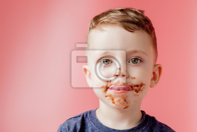 Fototapeta Little boy eating chocolate. Cute happy boy smeared with chocolate around his mouth. Child concept.
