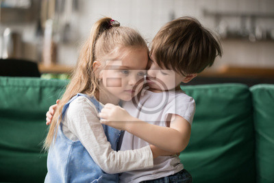 Fototapeta Little boy hugging consoling upset girl sitting on sofa, kid brother embracing sad sister apologizing or comforting, siblings friendship, preschool children good relationships and support concept